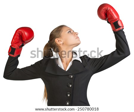 Businesswoman wearing boxing gloves, with her arms forward up, her head turned sideways. Isolated over white background