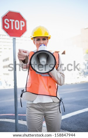 Businesswoman wearing builders clothes screaming in megaphone outdoors on urban background - stock photo
