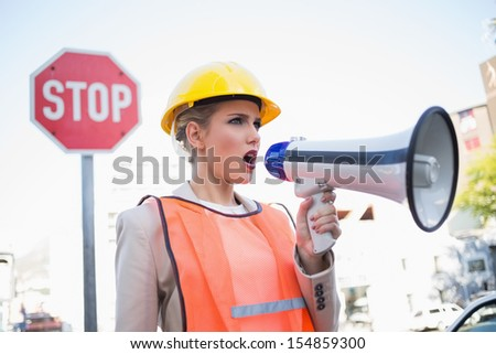 Businesswoman wearing builders clothes shouting in megaphone outdoors on urban background - stock photo