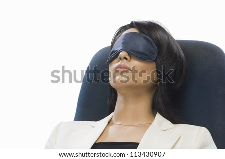 Businesswoman wearing eye mask and sleeping