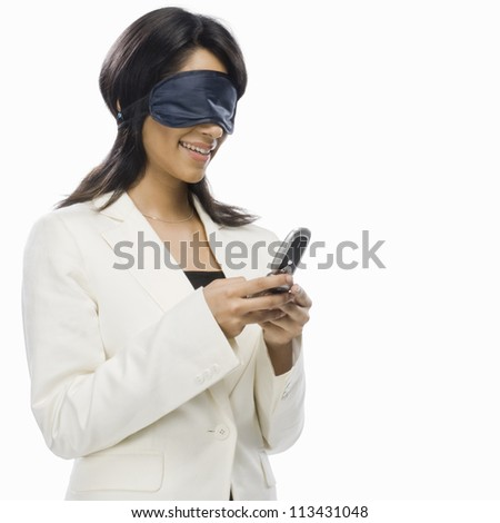 Businesswoman wearing eye mask and text messaging - stock photo