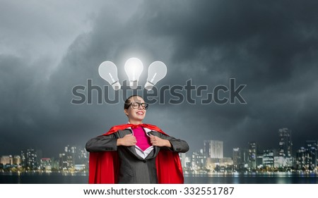 Businesswoman wearing red cape and opening her shirt like superhero