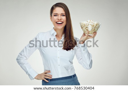 Businesswoman wearing white shirt holding glass bowl with pop corn. Isolated portrait.