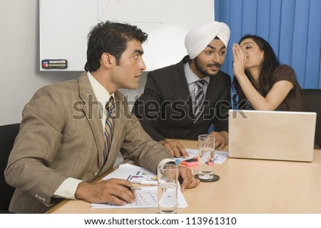 Businesswoman whispering in a board room - stock photo