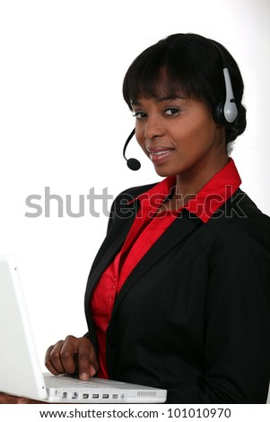 Businesswoman with a laptop and headset - stock photo