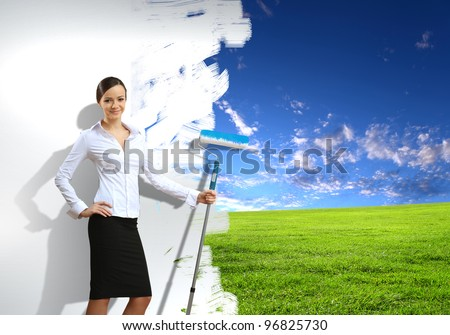 Businesswoman with a paint brush creating natural background - stock photo