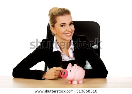 Businesswoman with a piggybank behind the desk.