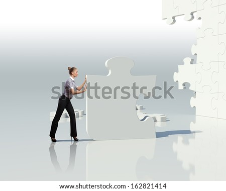 Businesswoman with a puzzle pieces on the background - stock photo