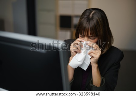 Businesswoman with a seasonal winter fever and chill blowing her nose on a white handkerchief as she sits in the shadows in her office - stock photo