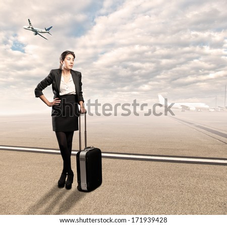 businesswoman with a suitcase standing at the airport - stock photo