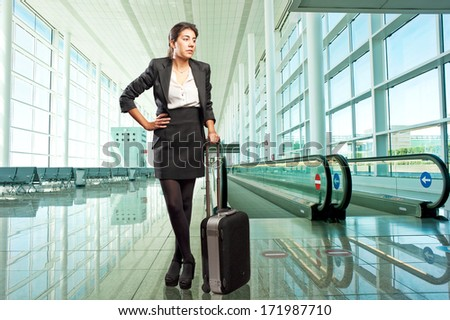 businesswoman with a suitcase standing in front of the airport travelator  - stock photo