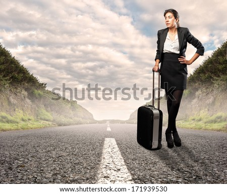 businesswoman with a suitcase standing on road - stock photo