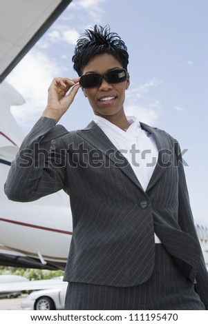 Businesswoman with airplane in background - stock photo