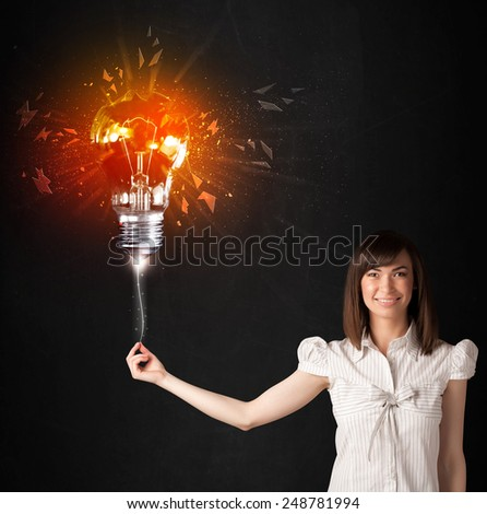 Businesswoman with an explosion bulb on black background - stock photo