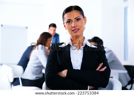 Businesswoman with arms folded standing in front of a metting - stock photo