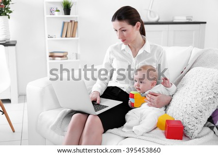 Businesswoman with baby boy on couch working from home using laptop - stock photo