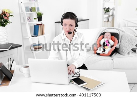 Businesswoman with baby boy working from home using laptop and headset - stock photo
