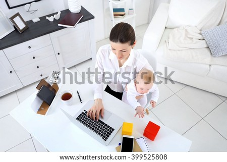 Businesswoman with baby boy working from home using laptop, view from above - stock photo