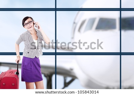 Businesswoman with big suitcase having a conversation on the phone, shot at airport