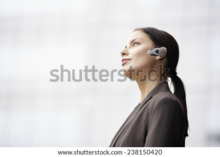Businesswoman with Bluetooth - stock photo