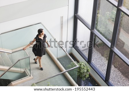 Businesswoman with briefcase pausing on stairway landing to look out