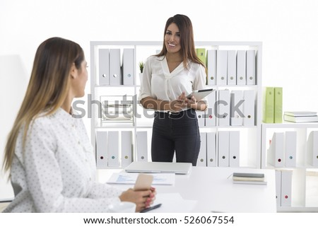 Businesswoman with brown hair is happy to see her supervisor and smiling broadly while holding a tablet. Concept of good bonding in a company