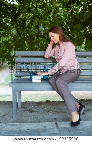 Businesswoman with computer laptop on the bench in the park - stock photo