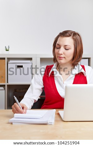 Businesswoman with computer taking notes at her desk in the office - stock photo