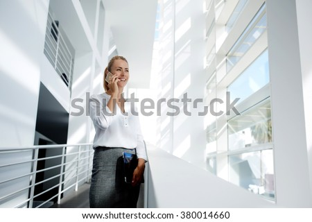 Businesswoman with digital tablet in hand talk on mobile phone with partner about successful project presentation, smiling female proud ceo speaking on cell telephone while standing in office interior - stock photo
