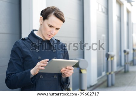 Businesswoman with digital tablet on front of warehouse