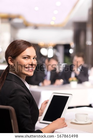 Businesswoman with digital tablet. Rear view of cheerful young woman in formalwear working on digital tablet and looking over shoulder while sitting at the restaurant - stock photo