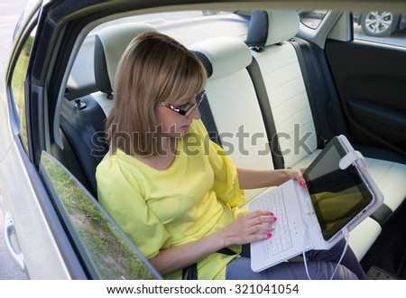 businesswoman with document and laptop in car - stock photo