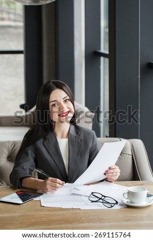 Businesswoman with documents and pen.