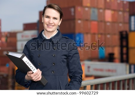Businesswoman with file folder in front of cargo container terminal