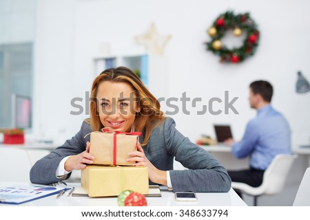 Businesswoman with gifts looking at camera in office on Christmas day