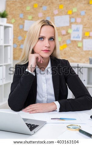 Businesswoman with head on hand in front of computer. Office at background. Concept of work. - stock photo