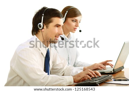 Businesswoman with headset in call center. Businessman in headsets on background