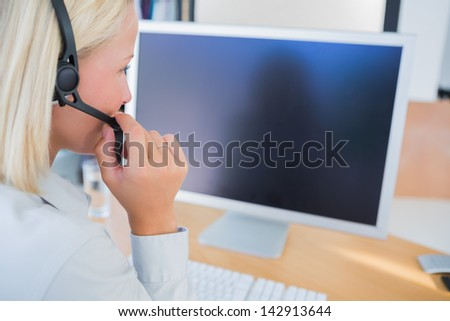Businesswoman with headset looking at blank computer screen at desk - stock photo