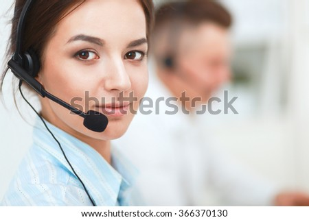 Businesswoman with headset smiling at camera in call center
