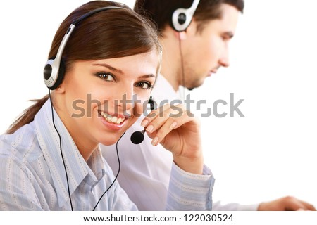 Businesswoman with headset smiling at camera in call center. Businessman in headsets on background - stock photo