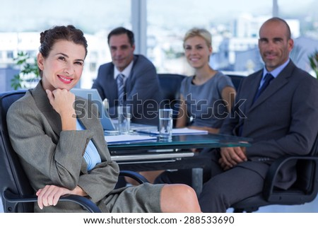 Businesswoman with her colleagues behind in the office - stock photo
