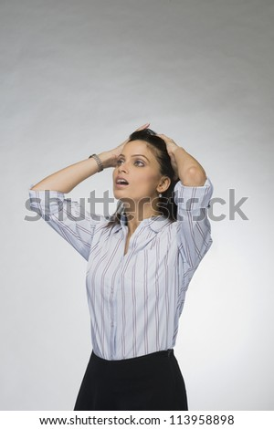 Businesswoman with her hands in her hair in shock - stock photo