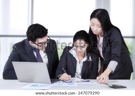 Businesswoman with her partners signing a business document in the office - stock photo