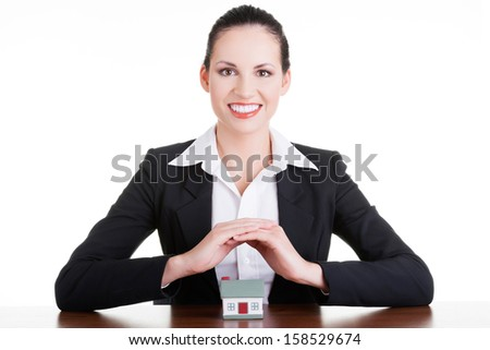 Businesswoman with house model over white - real estate loan or insurance concept  - stock photo