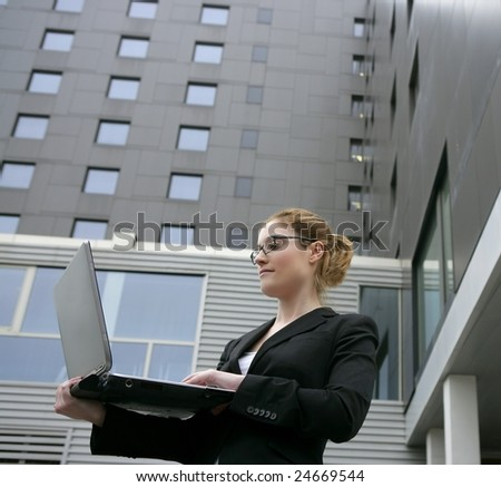 Businesswoman with laptop computer on the city, buildings on background - stock photo