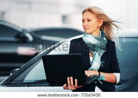 Businesswoman with laptop on a parking - stock photo