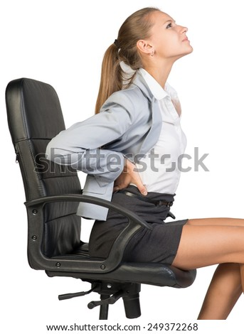 Businesswoman with lower back pain from sitting on office chair. Isolated over white background - stock photo