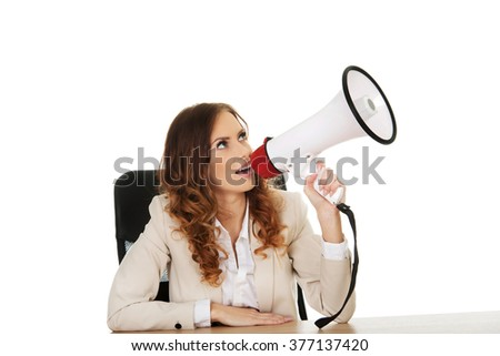 Businesswoman with megaphone by a desk. - stock photo