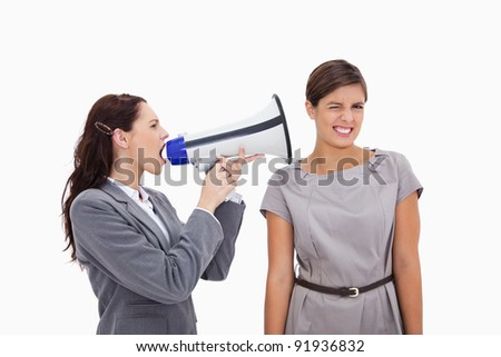 Businesswoman with megaphone yelling at colleague against a white background - stock photo