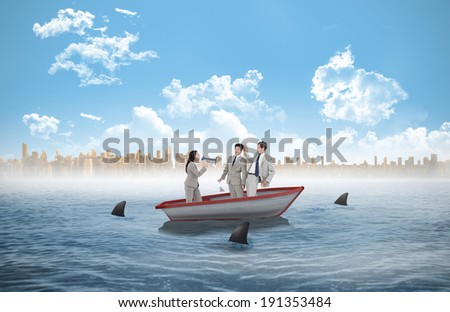 Businesswoman with megaphone yelling at colleagues against sharks circling a small boat in the sea - stock photo